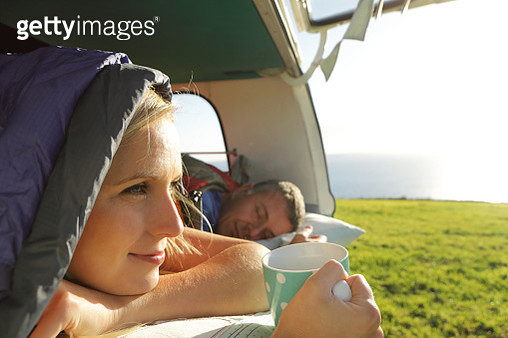 Couple laying in camper, woman looking at view - gettyimageskorea