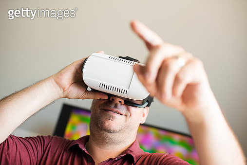 Smiling Man Pointing White Using Virtual Reality Simulator At Home - gettyimageskorea