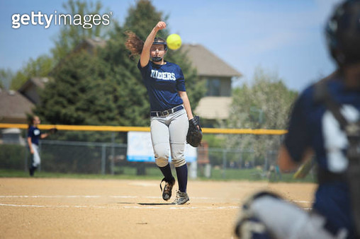 Teenage softball player throwing a pitch. - gettyimageskorea
