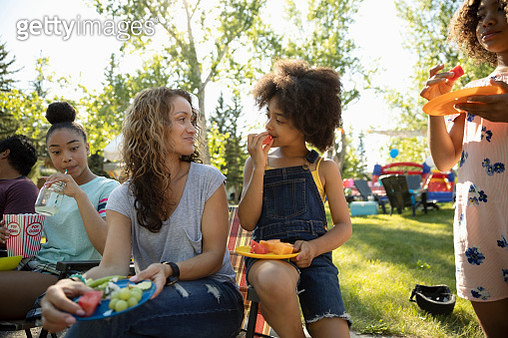 Mother and daughter eating fruit at summer neighborhood block party in park - gettyimageskorea