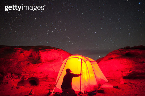 Man and tent under the night sky - gettyimageskorea