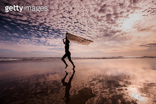 Beautiful woman with scarf feeling free on the beach. - gettyimageskorea