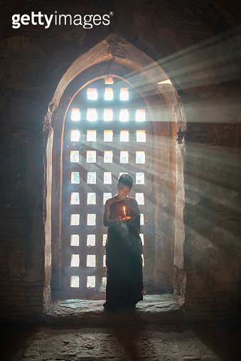 A young monk holding a candle in front of a window. - gettyimageskorea