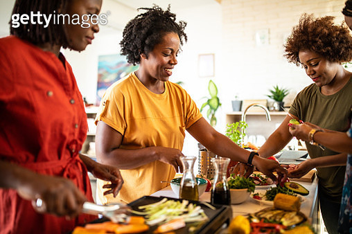 Joyful African women grilling vegetables on electrical barbecue at home in the kitchen - gettyimageskorea