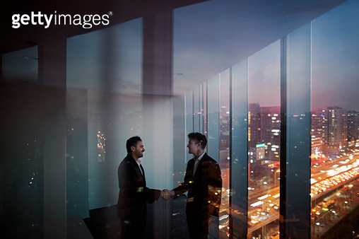 Businessmen shaking hands in office at night - gettyimageskorea