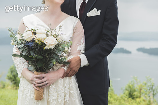 Unrecognizable bride and groom standing on scenic bluff - gettyimageskorea