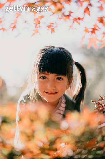 Cute young girl smiling enjoying autumn colour leaves - gettyimageskorea