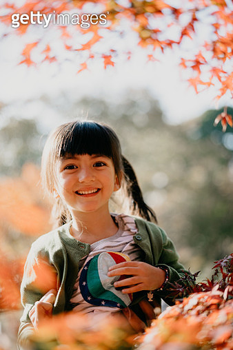4 year old mixed race girl smiling with red leaves of Japanese maple trees - gettyimageskorea