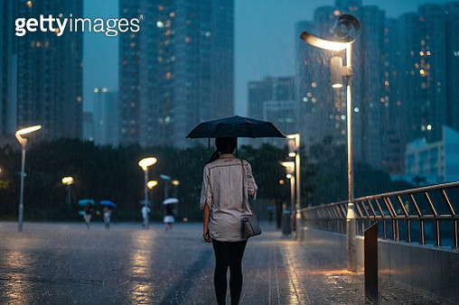 Woman standing under the heavy rain in city street - gettyimageskorea
