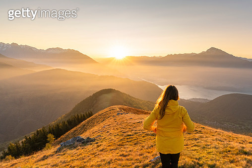 Woman gazing at Lake Como and mountains from high up, Italy. - gettyimageskorea