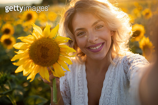 Portrait of beautiful young woman in sunflower field - gettyimageskorea