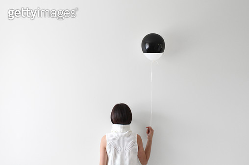 Rear view portrait of a woman facing wall holding balloon - gettyimageskorea