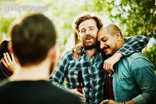 Two friends embracing during backyard party on summer evening - gettyimageskorea