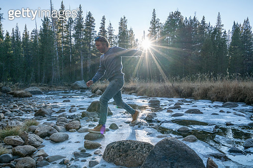 Hiker jumps from rock to rock crossing frozen river at sunset in pine tree forest, USA - gettyimageskorea