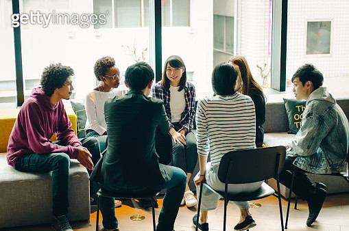 Young men and women discussing at the cafe. - gettyimageskorea