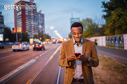 African-American businessman on a business trip using mobile phone calling a taxi. He is outdoor at the crowdy city street at the dusk - gettyimageskorea