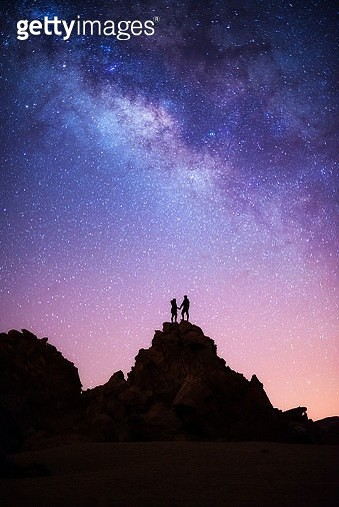 Silhouette Couple Standing On Rock Formation Against Sky At Night - gettyimageskorea