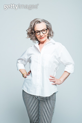 Elderly lady wearing white shirt, striped trousers and glasses standing with hands on hips against grey background, smiling at camera. Studio shot of female designer. - gettyimageskorea