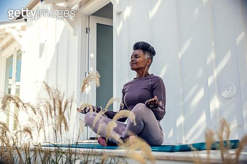 Mature woman meditating in backyard - gettyimageskorea