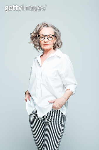 Elderly lady wearing white shirt, striped trousers and glasses standing against grey background, looking at camera. Studio shot of female designer. - gettyimageskorea