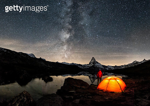 An illuminated tent under Milky Way at Matterhorn in Switzerland - gettyimageskorea