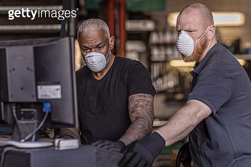 Two male mechanic essential workers wearing a face mask each during virus outbreak - gettyimageskorea