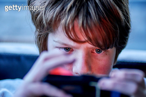 A close-up of a teenage boys eyes as he plays video games - gettyimageskorea