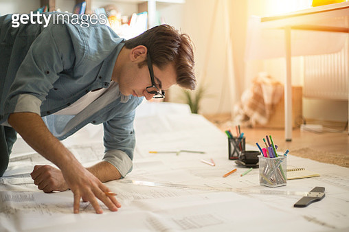 Architect working with blueprints in the home office. - gettyimageskorea