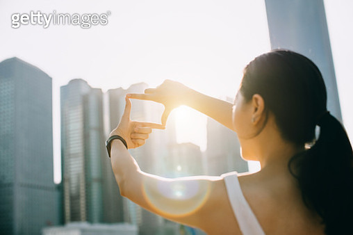Rear view of young woman frames the Hong Kong city skyline into a finger frame under a sunny sky - gettyimageskorea