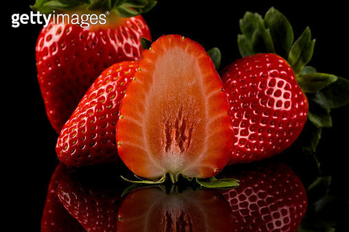 Red ripe strawberry fruits on a dark background - gettyimageskorea