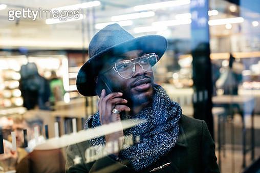 Portrait of confident businessman on cell phone behind windowpane - gettyimageskorea
