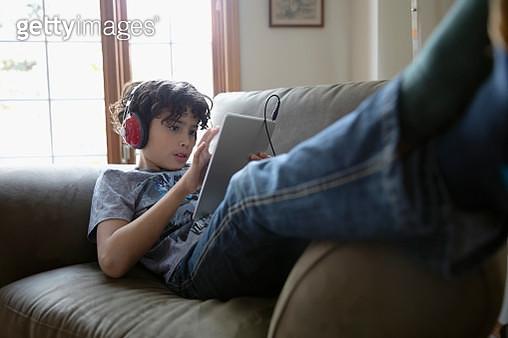 Latinx boy with headphones using digital tablet on sofa - gettyimageskorea
