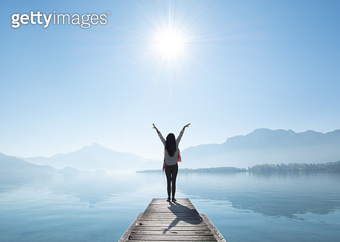 Full Length Rear View Of Woman With Arms Raised Standing On Pier By Lake Against Sky During Sunny Day - gettyimageskorea