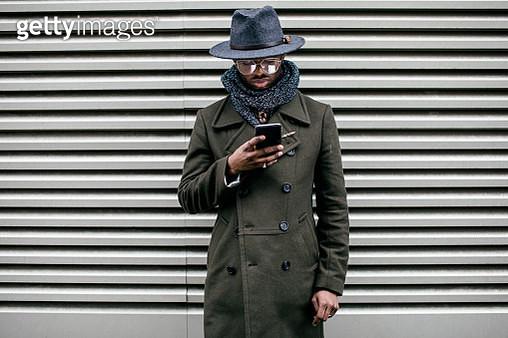 Man using mobile phone with Metal Rolling Door background - gettyimageskorea