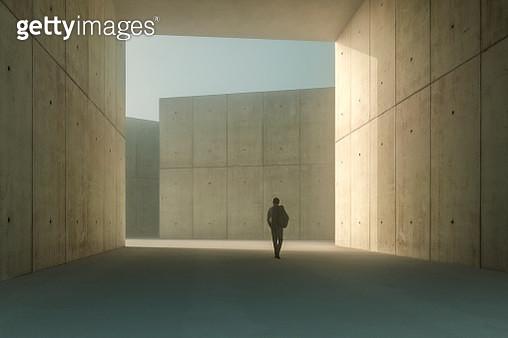 Businessman walking in concrete corridor - gettyimageskorea