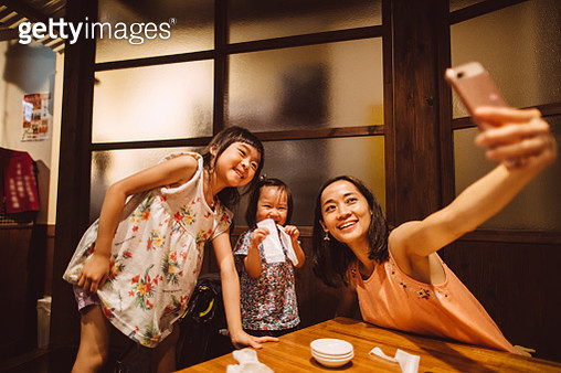 Pretty young mom taking selfies with little daughters joyfully in a Japanese restaurant in vacation - gettyimageskorea