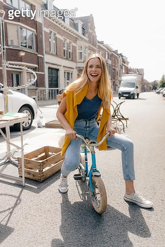 Belgium, Tongeren, happy young woman on a children's bicycle on an antique flea market - gettyimageskorea