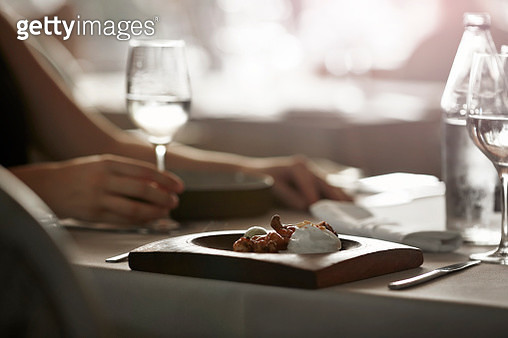 Fresh dish at restaurant with guest in back - gettyimageskorea
