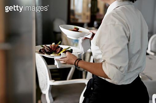 Waiter walking with dishes inside restaurant - gettyimageskorea