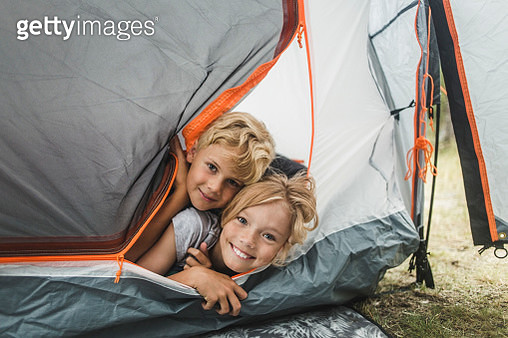 Portrait of smiling siblings peeking through tent at camping site - gettyimageskorea