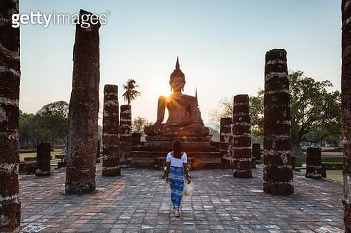 Asian woman visiting Wat Mahathat, Sukhothai, Thailand - gettyimageskorea