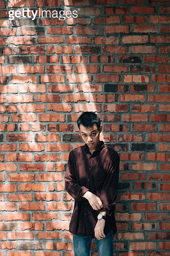 Portrait of young man standing with brick wall - gettyimageskorea