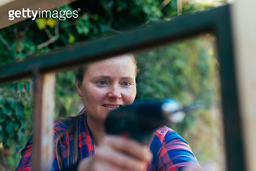 Woman using a screwdriver in diy project. - gettyimageskorea