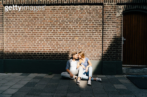 Netherlands, Maastricht, young couple having a break in the city sitting on sidewalk - gettyimageskorea