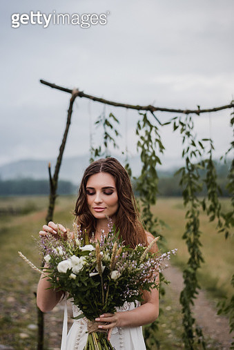 Bride Holding Bouquet While Standing On Field - gettyimageskorea