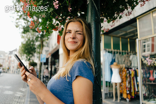 Netherlands, Maastricht, smiling young woman with cell phone in the city twinkling - gettyimageskorea