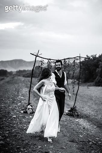 Bride And Bridegroom Holding Hands On Field - gettyimageskorea