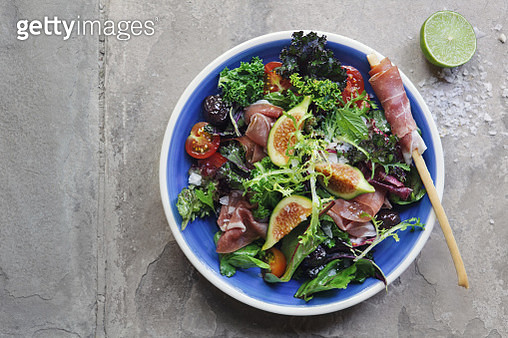 Mixed salad with tomatoes, kalamata olives, proscuittoes and figs - gettyimageskorea