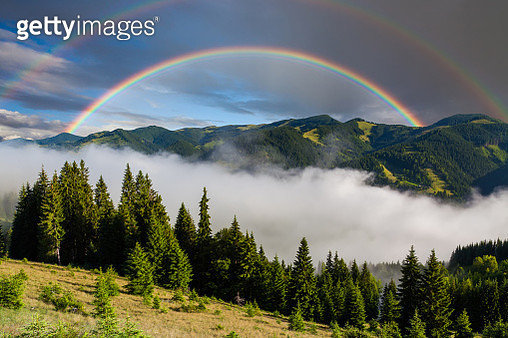 Rainbow over misty mountains in summer morning - gettyimageskorea