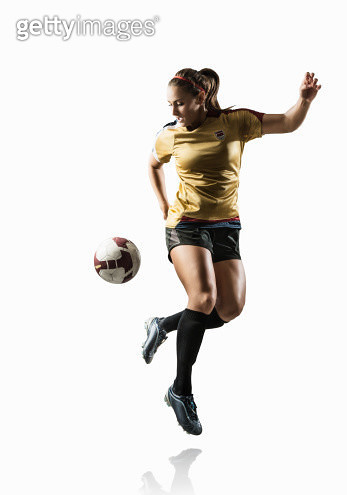 Studio shot of young female soccer player back kicking ball - gettyimageskorea
